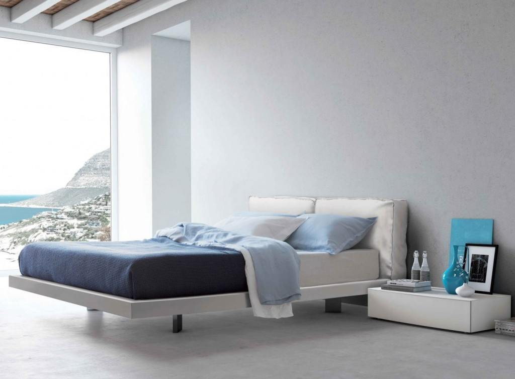 Modern white bed with blue sheets.