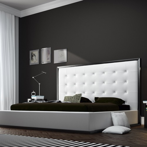 modern black and white bed with large headboard.