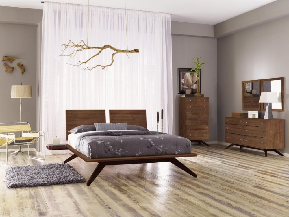 Modern bedroom furnished with wood dressers, bed frames, rugs and a lounge chair.